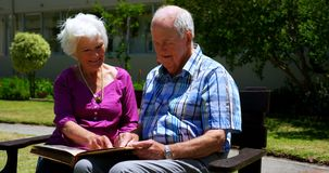 Front view of active Caucasian senior couple looking at photo album in the garden of nursing home 4k. Front view of active Caucasian senior couple looking at stock footage