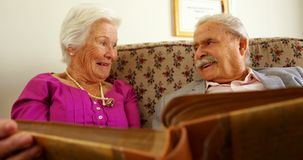 Front view of active Caucasian senior couple looking at photo album in nursing home 4k. Front view of active Caucasian senior couple looking at photo album in stock video footage
