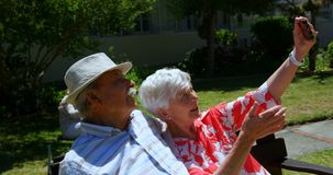 Front view of active Caucasian senior couple taking selfie with mobile phone in the garden of nursin. G home. They are sitting on a bench 4k stock video footage