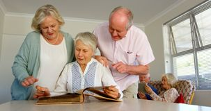 Front view of active Caucasian senior people looking at photo album in nursing home 4k. Front view of active Caucasian senior people looking at photo album in stock footage