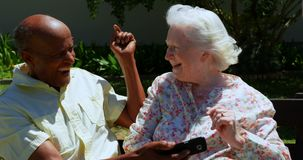 Front view of active mixed-race senior couple using mobile phone in the garden of nursing home 4k. Front view of active mixed-race senior couple using mobile stock footage