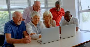Front view of active mixed-race senior people using laptop at nursing home 4k stock video