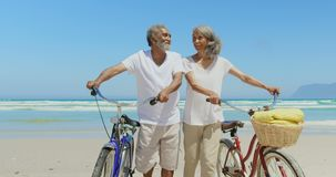 Front view of active senior African American couple with bicycle walking on beach in the sunshine 4k. Front view of active senior African American couple with stock video