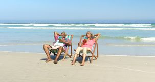 Front view of active senior African American couple having drinks on deckchair at beach 4k. Front view of active senior African American couple having drinks on stock footage