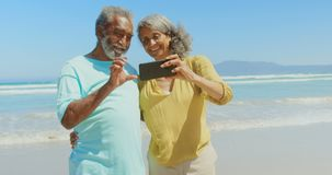 Front view of active senior African American couple taking selfie with mobile phone on the beach 4k. Front view of active senior African American couple taking stock footage