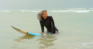 Front view of active senior African American female surfer sitting on surfboard in the sea 4k. Front view of active senior African American female surfer sitting stock footage
