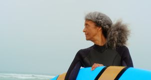Front view of active senior African American female surfer with surfboard standing on the beach 4k. Front view of active senior African American female surfer stock footage