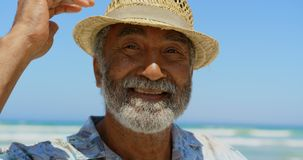 Front view of active senior African American man with hat standing on beach in the sunshine 4k. Front view of active senior African American man with hat stock video footage