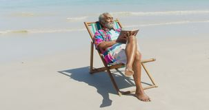 Front view of active senior African American man relaxing on deckchair with a book on the beach 4k. Front view of active senior African American man relaxing on stock footage
