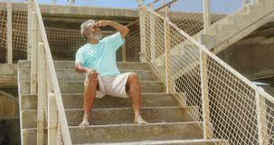 Front view of active senior African American man with shielding eye sitting on stair at promenade 4k. Front view of active senior African American man with stock video