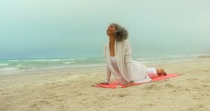 Front view of active senior African American woman doing yoga on exercise mat at the beach 4k. Front view of active senior African American woman doing yoga on stock video