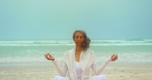 Front view of active senior African American woman doing yoga on exercise mat at the beach 4k. Side view of active senior African American woman doing yoga on stock video