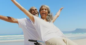 Front view of active senior African American woman sitting on man bicycle handlebars at beach 4k stock video