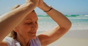 Front view of active senior Caucasian woman performing yoga on the beach 4k. Front view of active senior Caucasian woman performing yoga on the beach. She is stock footage