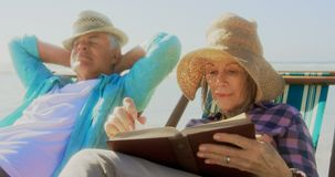 Front view of active senior Caucasian woman reading a book on the beach 4k stock video