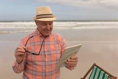 Happy senior man using digital tablet at the beach. Front view of active senior man using digital tablet on the beach. They seem happy. he wears a hat royalty free stock photos