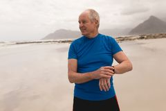 Happy senior man using smartwatch at the beach. Front view of active senior man using smartwatch at the beach with moutains in the background. He seems happy stock photo