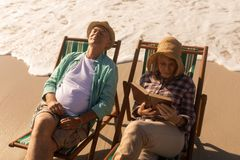 Senior woman reading a book while senior man relaxing on sun lounger at beach royalty free stock photo