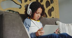 Front view of African american boy with headset playing game on digital tablet in lobby at hospital stock footage