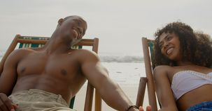 Front view of African american couple having fun together on the beach 4k. Front view of African american couple having fun together on the beach. They are stock video
