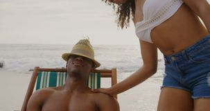 Front view of African american couple having fun together on the beach 4k. Front view of African american couple having fun together on the beach. They are stock video footage