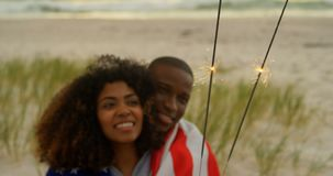 Front view of African american couple holding sparklers in hands at beach 4k. Front view of African american couple holding sparklers in hands at beach. They are stock footage