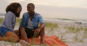Front view of African american couple interacting each other on the beach 4k stock video