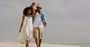 Front view of African american couple walking hand in hand on the beach 4k. Front view of African american couple walking hand in hand on the beach. They are stock footage