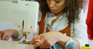 Front view of African American female fashion designer working with sewing machine in workshop 4k stock video footage