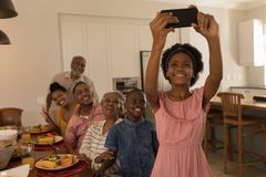 Girl taking selfie of family with mobile phone on dining table at home royalty free stock photography
