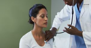 Front view of African american male doctor examining female patient in the ward at hospital stock footage