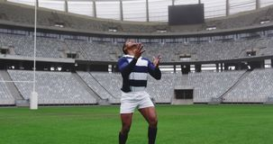 Male rugby player playing rugby match in stadium 4k. Front view of African American male rugby player playing rugby match in stadium. He is catching rugby ball stock footage