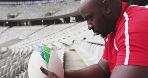 Male rugby player sitting with rugby ball in stadium 4k. Front view of African American male rugby player sitting with rugby ball in stadium. He is looking at stock video footage