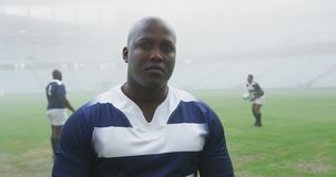 Male rugby player standing in stadium 4k. Front view of African american male rugby player standing in stadium. He is looking at camera 4k stock video footage