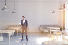 Front view of an African American man in a modern cafe with concrete walls. Royalty Free Stock Images