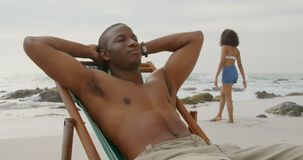 Front view of African american man relaxing with eyes closed on the beach 4k. Front view of African american man relaxing with eyes closed on the beach. Woman stock video footage