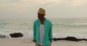 Front view of African american man walking with hands in pocket on the beach 4k. Front view of African american man walking with hands in pocket on the beach. He stock footage
