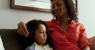 Front view of African american mother consoling her son in the lobby at hospital 4k