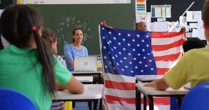 Front view of African american schoolboy explaining about American flag in the classroom 4k. Front view of African american schoolboy explaining about American stock footage