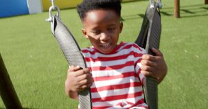 Front view of African American schoolboy playing on a swing in school playground 4k. Front view of African American schoolboy playing on a swing in school stock video