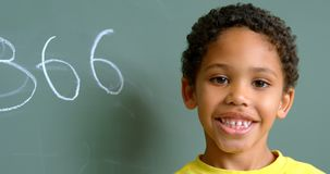 Front view of African American schoolboy standing against green chalkboard in classroom at school 4k. Front view of African American schoolboy standing against stock video