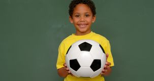 Front view of African American schoolboy standing with football against chalkboard in classroom 4k. Front view of African American schoolboy standing with stock footage