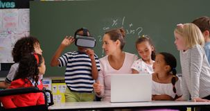 Front view of African american schoolboy using virtual reality headset with teacher and classmates i. N the classroom.  Female teacher using laptop 4k stock video footage