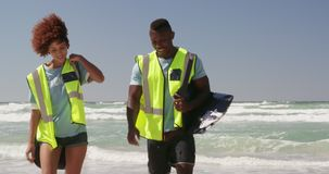 Front view of African american volunteers with garbage bag walking together on the beach 4k. Front view of African american volunteers with garbage bag walking stock footage