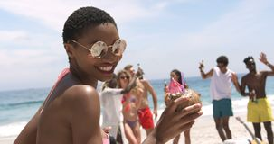Front view of African American woman dancing on the beach 4k. Front view of African American woman dancing on the beach. Male and female friends dancing in the stock video footage