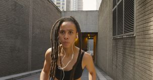 Front view of African American woman jogging in the city 4k