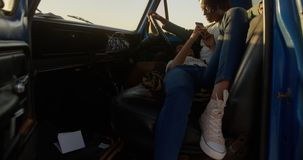Woman lying on mans lap in a pickup truck at beach 4k stock video footage