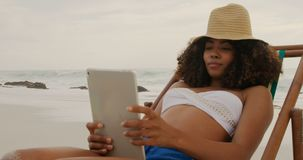 Front view of African american woman using digital tablet on the beach 4k. Front view of African american woman using digital tablet on the beach. She is stock video footage