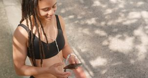 Front view of African American woman using mobile phone in the city 4k. Front view of African American woman using mobile phone in the city. She is listening stock video footage