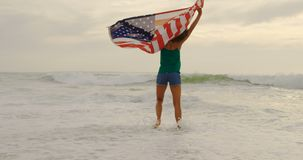 Front view of African American woman with waving American flag dancing on the beach 4k. Front view of African American woman with waving American flag dancing on stock video